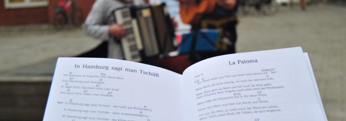 """Das Duo """"Kabel Jo"""" mit Akkordeon und Gitarre. Davor ein Liederbuch mit """"La Paloma"""""""