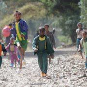 Kinder in Mekerie rennen und hüpfen auf der Straße lachend auf die Kamera zu